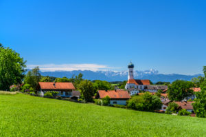 Germany, Bavaria, Upper Bavaria, Tölzer Land, Münsing, view of the village with the parish church of the Assumption against the Wetterstein Mountains with Zugspitze