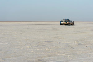 Four-wheel drive vehicles stand on the salt crust of the Assale Salt Lake, Hamedala, Danakil Valley, Afar Region, Ethiopia
