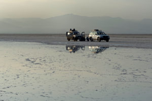 Two all-wheel drive vehicles stand in the pale evening light in front of a brine on the edge of the Assale Salt Lake, Hamedala, Danakil Valley, Afar Region, Ethiopia