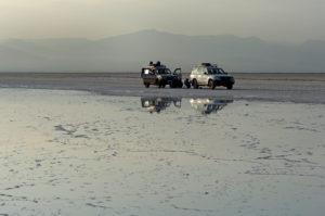 Zwei Allradfahrzeuge stehen im fahlen Abendlicht vor einer Salzlake am Rande des Assale Salzsee, Hamedala, Danakil Senke, Afar Region, Äthiopien
