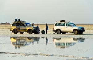 Zwei Allradfahrzeuge mit Begletpersonal stehen vor einer Salzlake am Rande des Assale Salzsee, Hamedala, Danakil Senke, Afar Region, Äthiopien