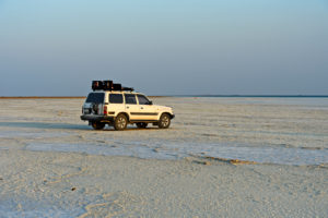 4x4 vehicle of a local tourism company stands on the salt crust of the Assale Salt Lake, Hamedala, Danakil Valley, Afar Region, Ethiopia