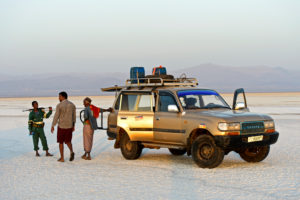 Local guide, driver and security guard stand next to a four-wheel drive vehicle of a local tourism company on the salt crust of the Assale Salt Lake, Hamedala, Danakil Valley, Afar Region, Ethiopia