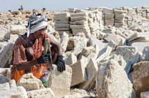 Einheimischer Mann behaut Salzblöcke in einem Salzsteinbruch am Assale Salzsee, Danakil Depression, Afar Region, Äthiopien