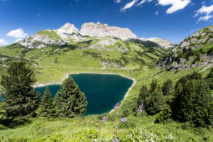 Formarinsee in front of red wall, clouds, blue heavens, summits