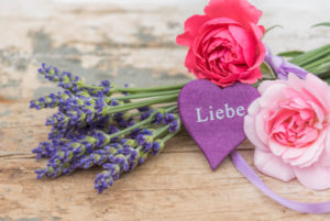 bouquet of lavender and small moss roses on old wooden board with heart and writing 'Liebe'
