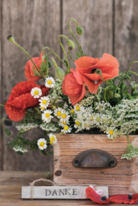 """Flower arrangement made of poppy blossoms, camomile and other field flowers in an old wooden box with grasp, sign with the writing """"DANKE"""""""