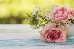 Flower arrangement of pink roses and small white blossoms in a small old white cup on wooden board with green background light,