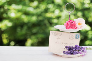 floral still life with lavender, roses and old letter in the green back light on old wooden board