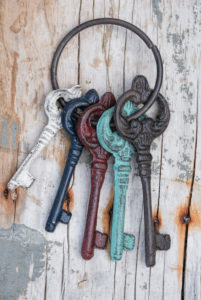 key ring with coloured old keys on old weather-beaten wooden board