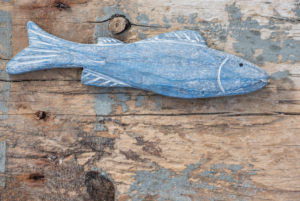Maritime still life, blue wooden fish on old weather-beaten wooden board