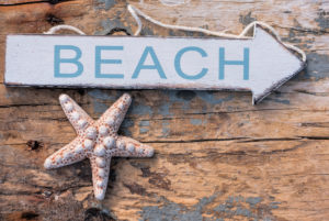 """Maritime still life, sign """"Beach"""" and starfish on old wooden board"""