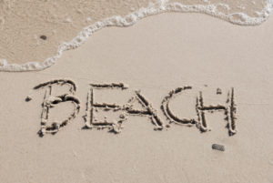 Beach' written in sand, horizontal photograph with small wave washed up on the sand,