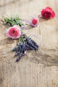 Flower decoration of lavender and pink roses on old wooden board,