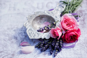 Florale decoration, old silver tea strainer with lavender and pink roses and petals