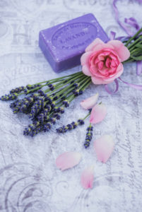Florale decoration, pink rose on lavender, lavender soap, single petals in the foreground