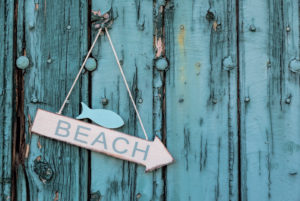 Arrow direction Beach on old turquoise wooden board, maritime decoration,