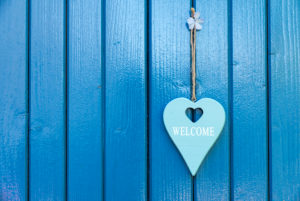 Turquoise heart with saying 'Welcome' on a blue door