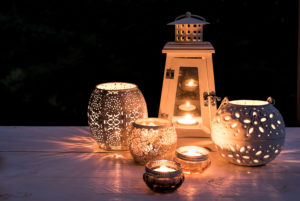 Different lanterns and lights are lightning on white wooden board in the darkness,