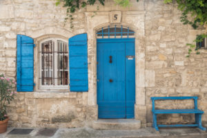 Wall of a house made of natural stone, window, blue shutters, door and bench in the South of France,