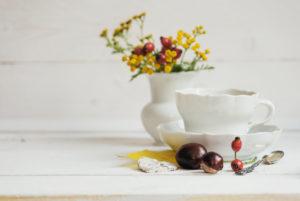 floral autumnal still life with coffee cover and flower vase with yellow blossoms and red rose hips
