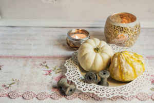 Autumnal still life with pumpkins in a white bowl, tea lights in background,