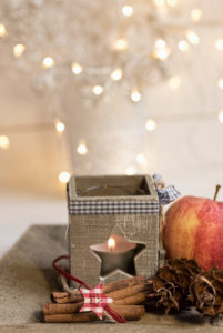 Christmas Still Life with tea light holder, apples, cinnamon and cones sorts Christmas decorations,