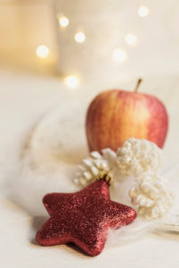 Christmas Still Life with Red Star, cones and apple, the background glittering lights,