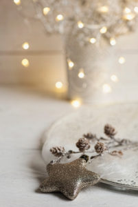 Christmas Still Life with golden glitter star and cones on a white plate, in background Christmas Lights,
