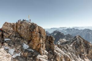 Bergsteiger am Gipfelkreuz der Zugspitze