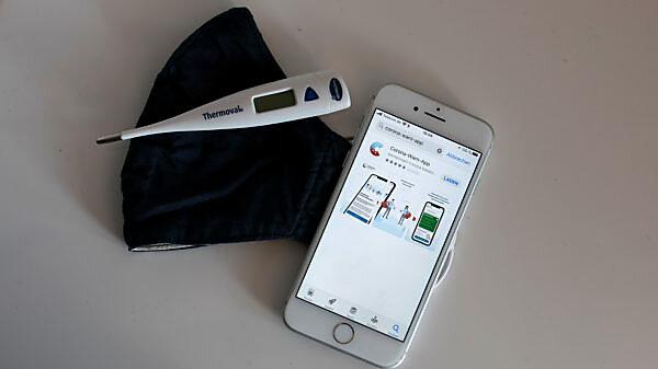 Corona-Warn-App auf iphone und Mund-Nasen-Maske auf Tisch mit Fieberthermometer
