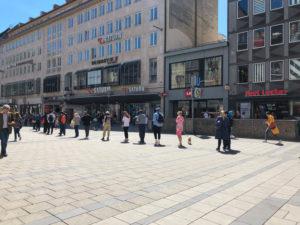 Menschen shoppen während Corona mit Sicherheitsabstand, Menschenschlange