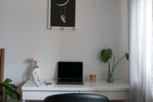 Home-Office Schreibtisch mit Smartphone und Deko-Astronaut