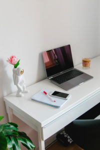 Home office desk with smartphone and decorative astronaut