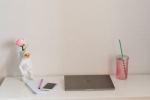 Home office desk with laptop, smartphone, drink and decorative astronaut