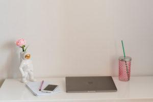 Home-Office Schreibtisch mit Laptop, Smartphone, Getränk und Deko-Astronaut