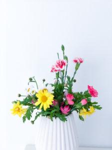 Frühlingsblumenstrauss mit Margeriten und Ranunkel, bunter Blumenstrauss in weißer Vase, Instagram-Style,