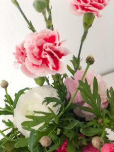 Frühlingsblumenstrauss mit Nelken und Ranunkel, bunter Blumenstrauss in weißer Vase, Instagram-Style,