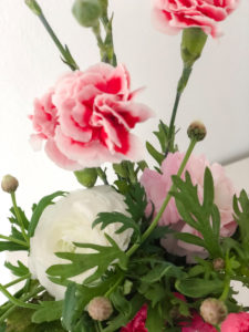 Spring bouquet with carnations and ranunculus, colorful bouquet in a white vase, Instagram style,
