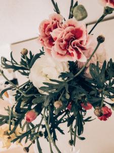 Frühlingsblumenstrauss mit Nelken und Ranunkel, bunter Blumenstrauss in weißer Vase, Instagram-Style,  dunkle Bearbeitung