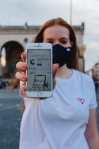 Rothaarige Frau mit Corona-Warn-App auf iphone in München auf Odeonsplatz