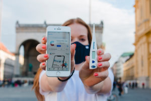 Red-haired woman with Corona warning app on iphone in Munich on Odeonsplatz