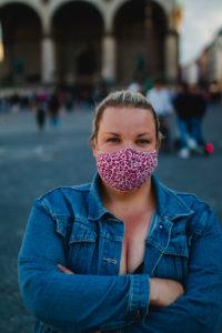 Blonde Frau mit Maske zu Corona-Zeiten auf vollem Odeonsplatz in München