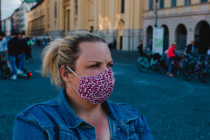 Blond woman with mask in Corona times on full Odeonsplatz in Munich