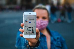 Blond woman with corona warning app on Odeonsplatz in Munich