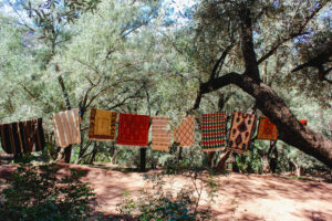 Berber carpets in forest in Ouzoud on clothesline