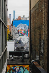 Sightseeing along the High Line in Manhattan with a view of graffiti and apartment buildings