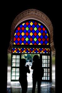 Bahia Palace Marrakesch, zwei Menschen / Silhouetten von Menschen unter buntem Fensterglas