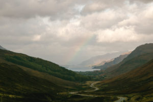 Landschaft in Schottlands Highlands, Regenbogen über Tal