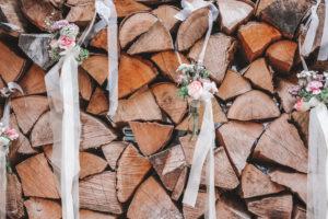 Detailaufnahme, Hochzeit, Holzstapel, Holzscheite geschmückt mit kleinen Blumensträußen